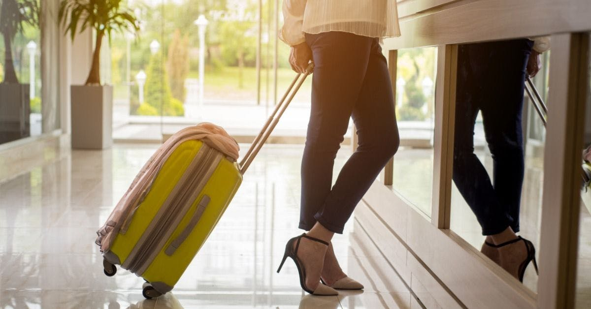 Woman with suitcase enjoying Pruvo facility at hotel booking